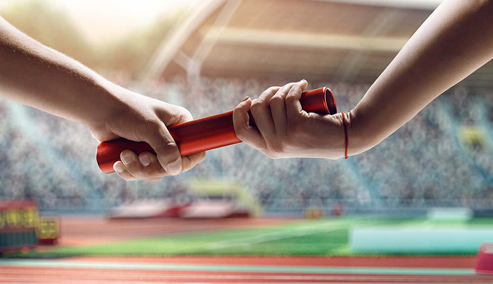 Close up of exchanging relay baton on a race